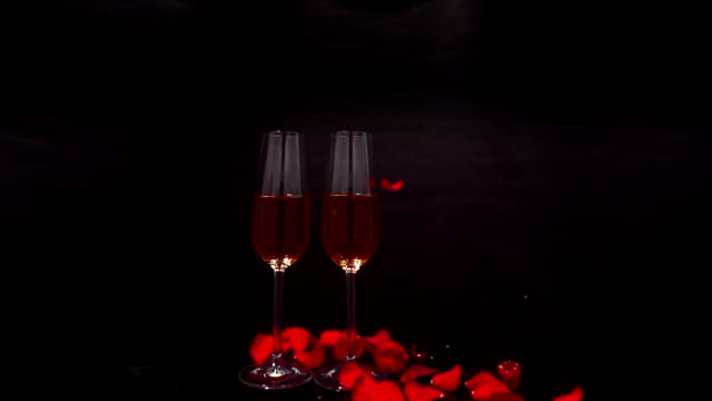 two champaign glasses rotate as rose petals fall around them in slow motion. - david ewing 個影片檔及 b 捲影像