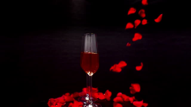 two champaign glasses rotate as rose petals fall around them in slow motion. - david ewing stock videos & royalty-free footage