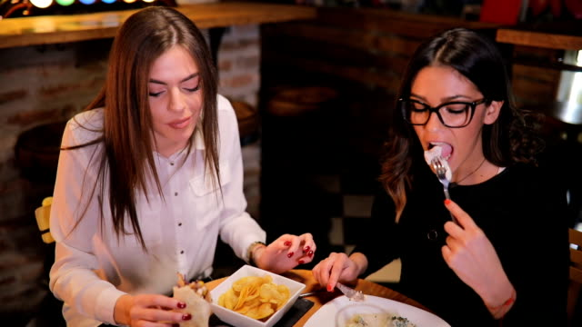 two charming ladies eating dinner in pub - dining stock videos & royalty-free footage