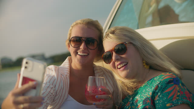 slo mo two cheerful women take selfie while relaxing on a boat - wilmington north carolina stock videos & royalty-free footage