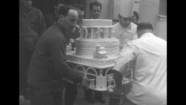 two chefs and two others gingerly carry the base of an elaborate wedding cake through a door / a crown shaped wedding topper is carried / pan down... - celebrities video stock e b–roll