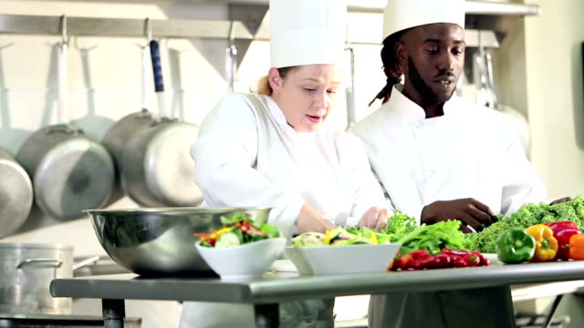 two chefs in commercial kitchen preparing food - caterer stock videos and b-roll footage