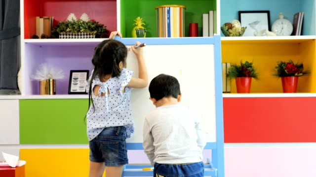 two child drawing on easel board at class - lavagna video stock e b–roll