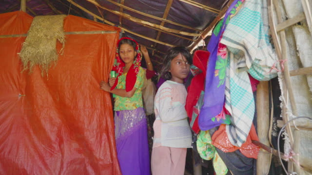 Two children and their mother stand inside their tent in Kutupalong refugee camp in Bangladesh Children make up over 50% of those in the camps and...
