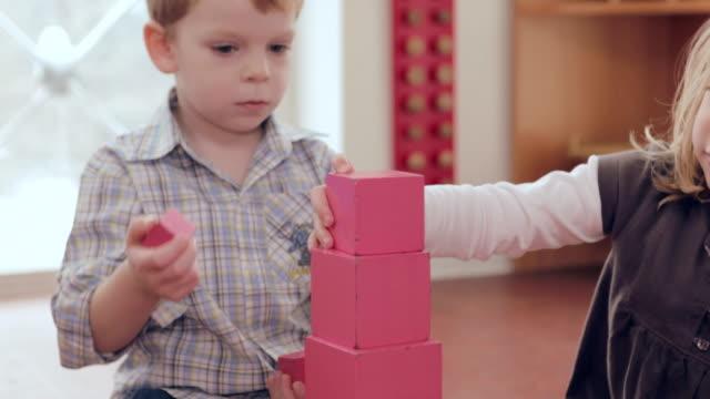 ms two children building up pink tower on carpet / potsdam, brandenburg, germany - platzieren stock-videos und b-roll-filmmaterial