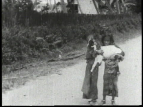1932 ws two children carrying a goat on the road then setting him down / china  - 1932 stock videos and b-roll footage