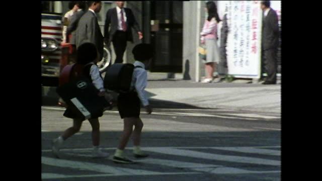 ws two children cross the road in hiroshima, japan; 1975 - 日本の学生服点の映像素材/bロール