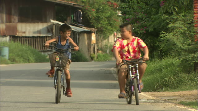 Two children cycling in the village of Aranik.