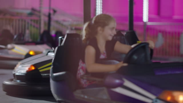 two children drive bumper cars at a summer carnival - gala stock videos & royalty-free footage