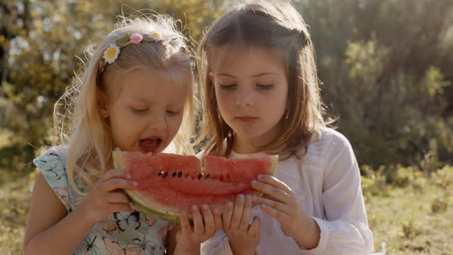 Two children eating watermelon