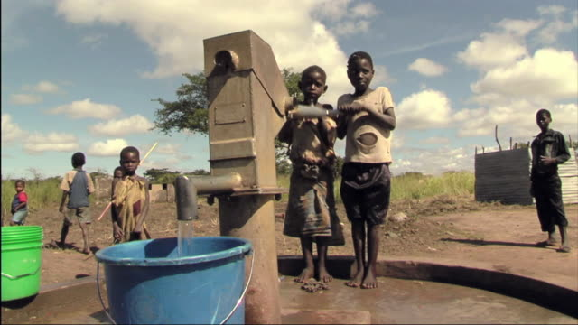 ws two children filling bucket with water at hand pump / mozambique - povertà video stock e b–roll