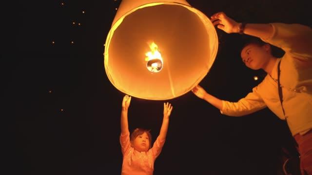vídeos de stock e filmes b-roll de two children girl in thai dress with sky lantern in loi krathong festival chiang mai thailand - lanterna de papel