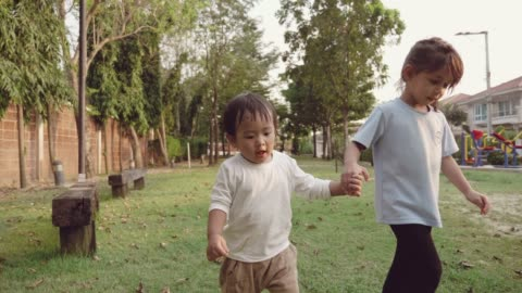 two children holding hands, walking together outdoors - brother stock videos & royalty-free footage