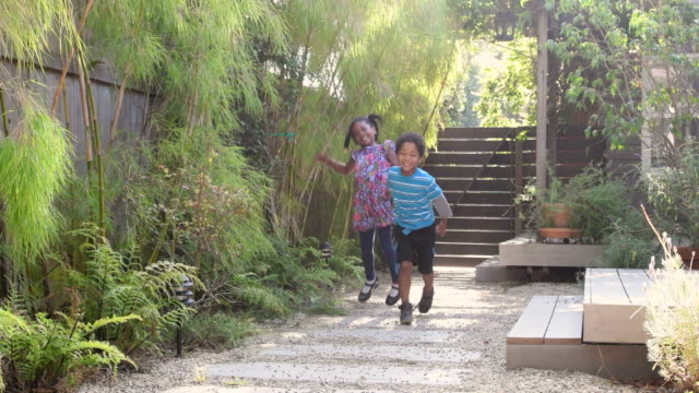 two children in garden holding hands and jumping towards camera - garden path stock videos and b-roll footage