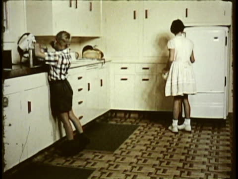 1955 MONTAGE MS CU Two children in kitchen, girl pouring water into teapot, boy looking at magazine on kitchen counter / New Zealand / AUDIO