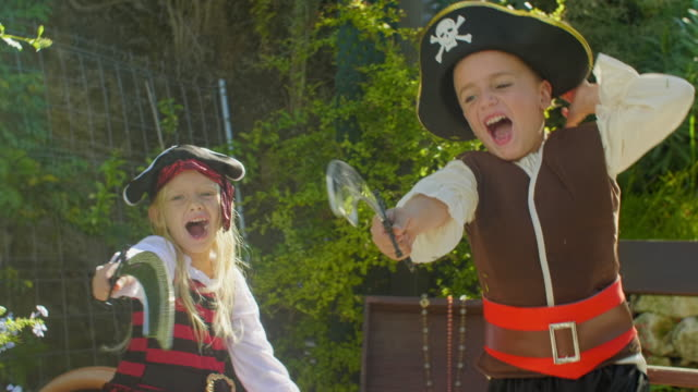 two children in pirate costumes ambushing from behind tree - seeräuber stock-videos und b-roll-filmmaterial