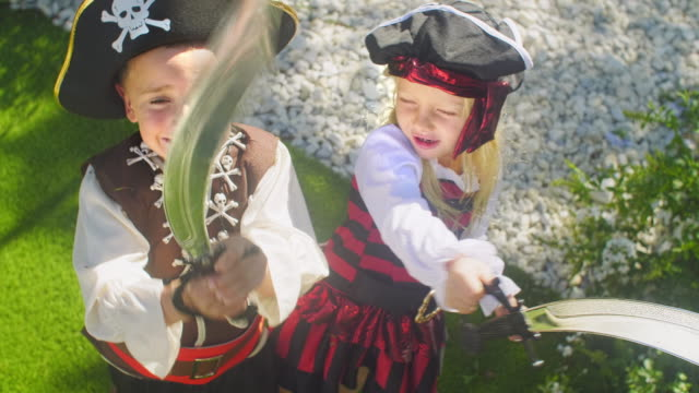 vídeos y material grabado en eventos de stock de two children in pirate costumes playing with toy swords - disfrazar