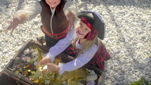 Two children in pirate costumes playing with treasure chest and throwing gold coins in the air
