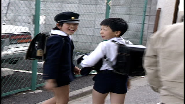 Two Children In School Uniforms Walking and Waving at Camera in Tokyo