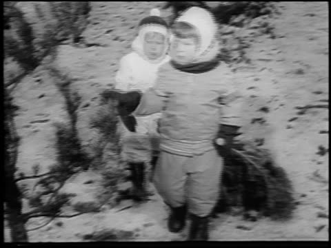B/W 1964 two children in Winter coats + hats dragging Christmas tree in snow / newsreel
