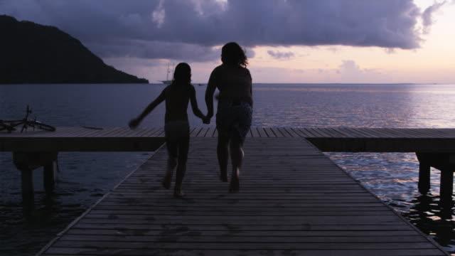 vídeos de stock, filmes e b-roll de two children jumping off a pier into the ocean - huahine island