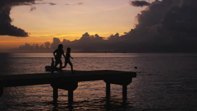 vidéos et rushes de two children jumping off a pier into the ocean - île d'huahine