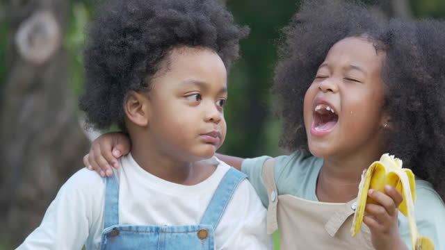 two children of african ethnicity age 3-4 year old having fun laughing eat banana together while spends time on a picnic outdoor.waist up and close-up portraits concept. - video portrait stock videos & royalty-free footage