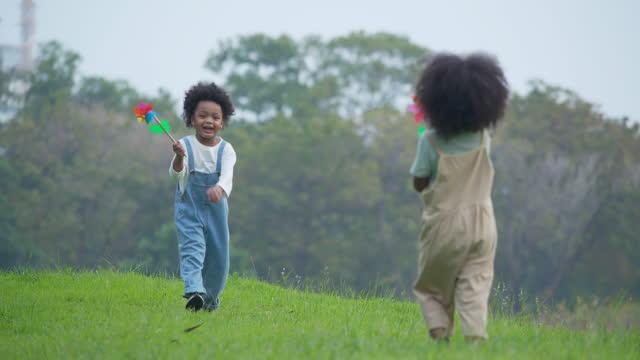 vidéos et rushes de deux enfants d'origine africaine âgés de 4 à 5 ans s'amusent et jouent ensemble avec une éolienne tout en passe du temps pour des vacances d'été de pique-nique à l'extérieur. mode de vie durable,concept de pique-nique. - 4 5 ans