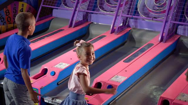 vídeos de stock, filmes e b-roll de duas crianças jogando fliperama, bola rolando - termo esportivo