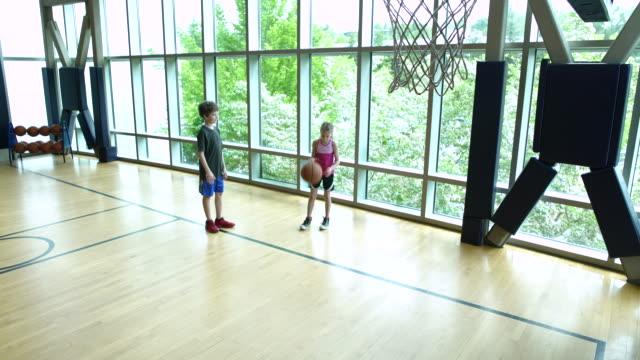 vídeos de stock e filmes b-roll de two children playing basketball in a gym - 6 7 anos