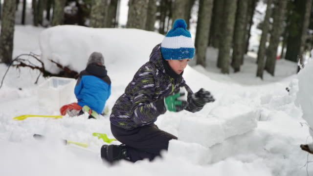 slo mo two children playing outside in the snow - building activity stock videos & royalty-free footage