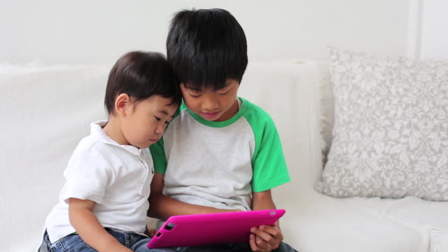 Two children playing with a tablet together on the sofa at home