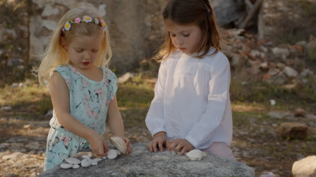 two children playing with shells and stones - seashell stock videos & royalty-free footage