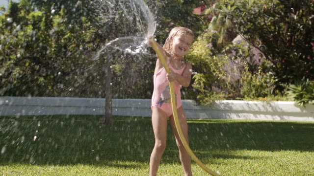 two children playing with water hose in garden - hose stock videos & royalty-free footage