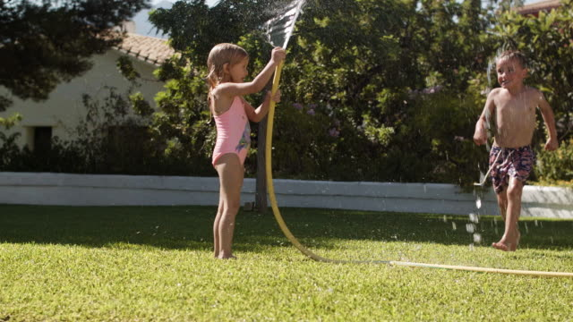 two children playing with water hose in garden - lawn stock videos & royalty-free footage