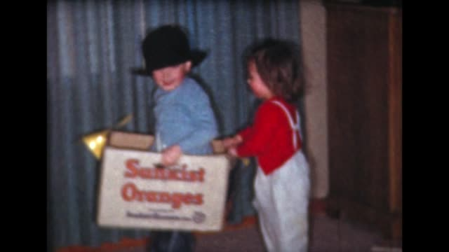 vídeos y material grabado en eventos de stock de 1961 two children ride cardboard box-horse - sombrero