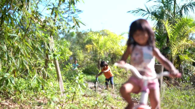 two children riding a bicycle in a rural place - indigenous peoples of the americas stock videos & royalty-free footage