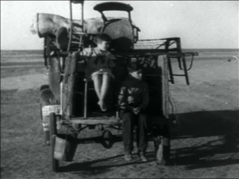 B/W 1936 two children riding on back of cart pulled by car driving on barren plain / Dust Bowl