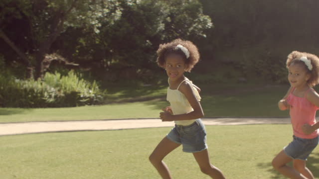 two children running around camera in park - shorts stock-videos und b-roll-filmmaterial