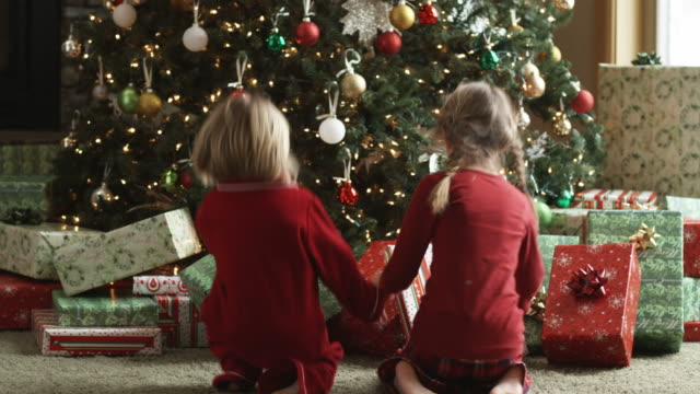 two children running towards their presents on christmas morning - weihnachten stock-videos und b-roll-filmmaterial