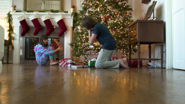 two children shaking christmas presents - christmas stocking stock videos and b-roll footage