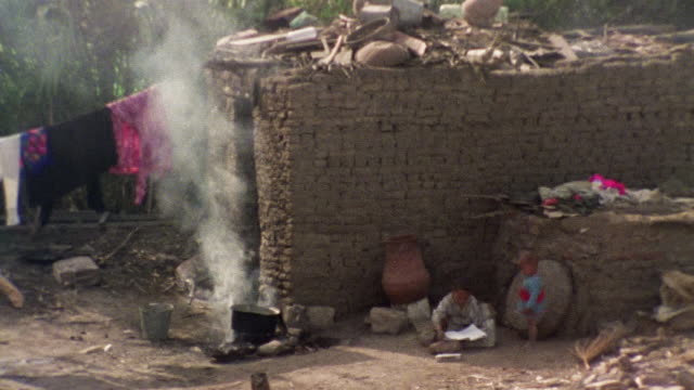 HA WS Two children sitting near steaming cauldron outside brick dwelling / Egypt