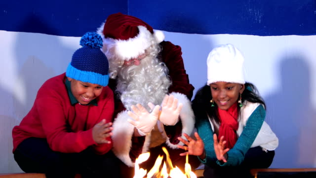 Two children sitting with Santa Claus by fire