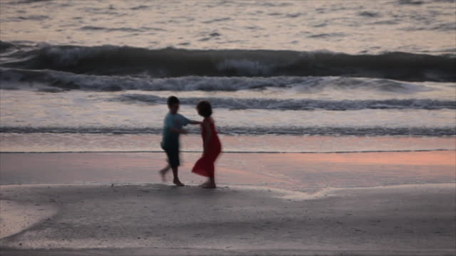Two children twirl on a Florida beach at sunset.