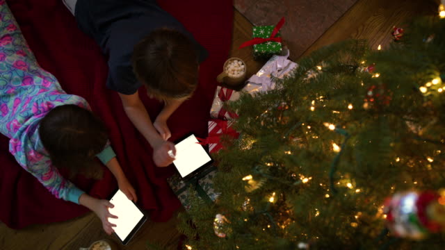 two children using tablets under a christmas tree - pigiama video stock e b–roll