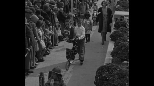 two children walking down street holding dolls / line of children riding bicycles people watching / small girl riding on small float with doll... - singing contest stock videos and b-roll footage