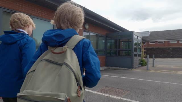 stockvideo's en b-roll-footage met two children walking to school - alleen jongens