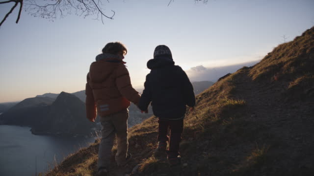 two children walking towards viewpoint at sunset - active lifestyle stock videos & royalty-free footage