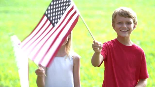 vídeos de stock e filmes b-roll de two children waving american flags - dia do trabalhador