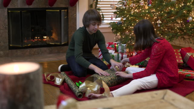 two children wrapping a christmas present - 10 seconds or greater stock videos & royalty-free footage